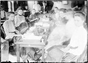 Eight girls sewing by hand, looking at the camera during a sweatshop inspection DN-0001247, Chicago Daily News negatives collection, Chicago History Museum